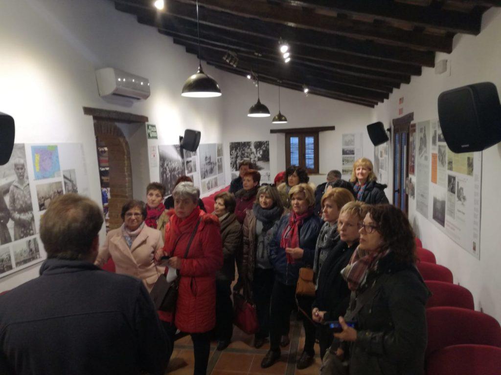 Integrantes de las asociaciones de mujeres de Jaén atienden las explicaciones de Andrés REbolledo en la exposición sobre el exilio de la Casa de la Memoria.